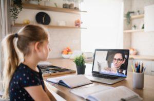 Young girl talks to her teacher via Zoom video app